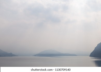 Foggy mountain misty islands covered with fog, calm sea lake landscape background, sunlight in cloudy sky scenery morning weather, scenic tranquil nature lake horizon. Italy, Lombardia, Riva di Solto