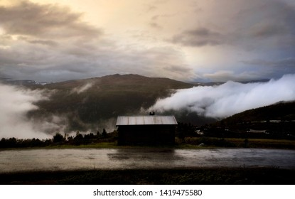 Foggy mountains and lonely cabin Jotunheimen Norway