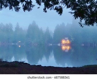 Foggy night on the lake. With overhanging branches framing the top and a bit of ground framing the bottom early evening fog is setting in with trees & lights from a house reflected on the calm water.