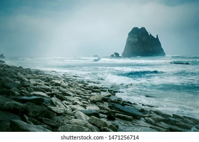 Foggy Papuma beach with frothy waves and stones in Jember at East Java, Indonesia