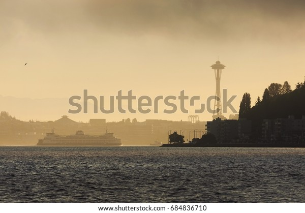 Foggy Seattle Morning. A ferry boat heads to downtown Seattle, Washington passing Alki Point on a foggy summer morning