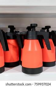 Foggy spray plastic bottles in red and black color on white shelf. Equipment for multipurpose cleaning.