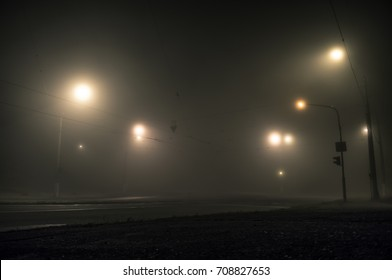 Foggy street lights misty with night deserted road