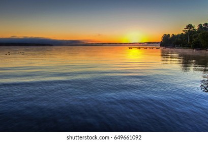 Foggy Summer Lake Sunrise Panorama. Sunrise over Lake Superior on a foggy summer morning with a small wooden dock at the horizon.