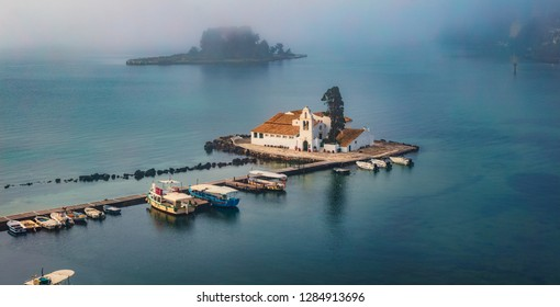Foggy summer view of Vlacherna Monastery. Stunning morning cityscape of Kerkira town, capital of Corfu island, Greece, Europe. Amazing seascape of Ionian Sea. Traveling concept background.