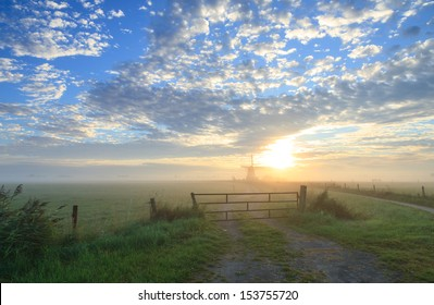 Foggy sunrise at a fence in the Netherlands near a windmill.