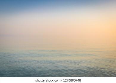 Foggy sunrise over the sea - background