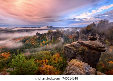 Foggy sunrise in the Saxon Switzerland, Germany, view from the Bastei lookout point. The Bastei is a tourist attraction for over 200 years.
