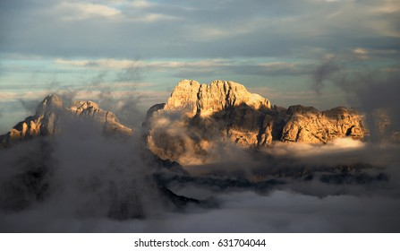A foggy sunset in Italian Alps, Dolomiti mountain, blue cloudy sky, fogg as a sea and red steep rocky walls of a high peak