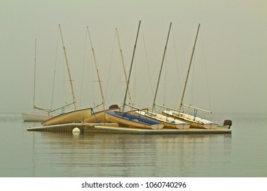 Foggy view of boats resting on a wharf in an ocean harbor