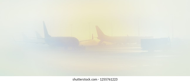 Foggy weather in an airport - airplanes on an airfield in the morning haze. Landscape with silhouettes of aircrafts in a fog at sunrise. Soft background for  air traveling or air transport.
