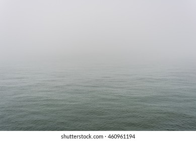 Foggy weather in the middle of the ocean with small waves.