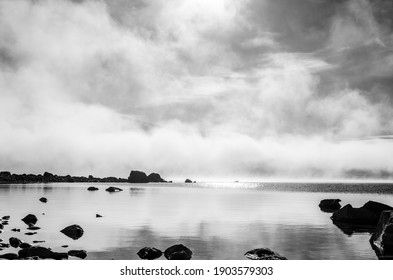 A foggy winter day at the Lake Tekapo on New Zealand's South Island, snow-capped mountains, the Southern Alps, in the distance, black and white.