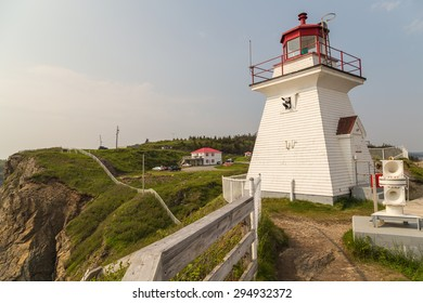 Foghorn in foreground  of historic Cape Enrage Lighthouse and Tourist Complex.