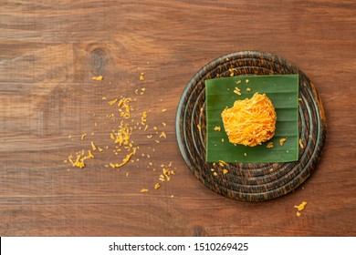 Foi Thong,  (Shredded Egg Yolk Tart) Thai desserts ingredients, used Egg yolks and sugar are boiled in sweet syrup and then formed into hairlike shapes on a wooden plate. Top view.