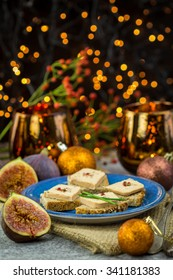 Foie gras on wholewheat bread with juicy ripe figs served as snacks at a festive celebration with colorful party lights in the background