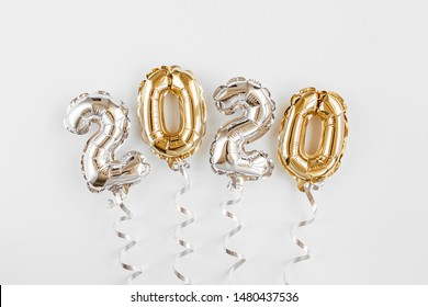 Foil balloons in the form of numbers 2020. New year celebration. Gold and silver Air Balloons. Holiday party decoration.