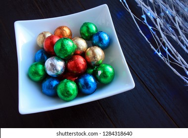 Foil wrapped candy Chocolate balls inside a white bowl. White branches with blue lights. On  a black wooden background.