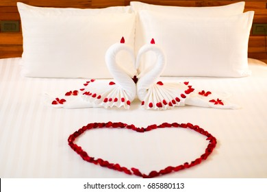 fold a towel couple swan for decorations with rose petals on wedding bed.
