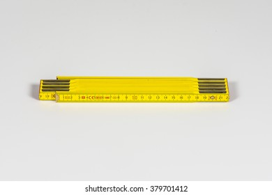 An fold-able yellow European ruler, two meter long, on white background.