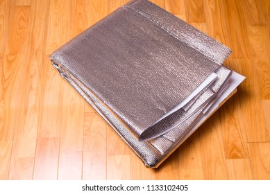 Folded aluminum foil bubble heat insulation sheet on a wood floor