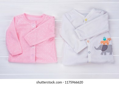 Folded baby clothes, top view. Pink and white sleepwear toddler shirts on white wood.