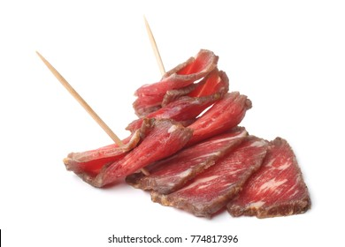 Folded beef carpaccio marinated in red wine on white background