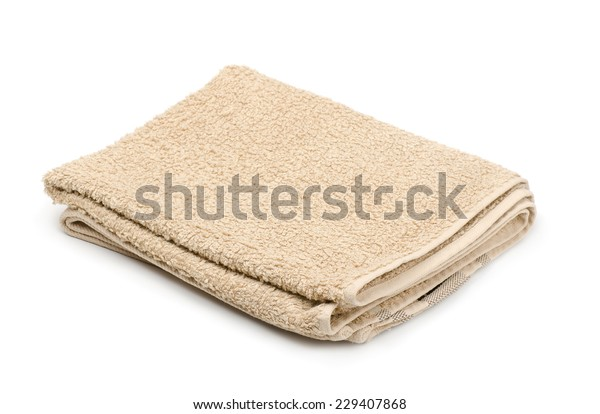 Folded beige terry towel isolated on white