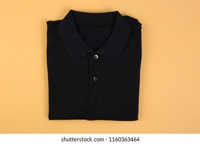 Folded black shirt polo on orange pastel background