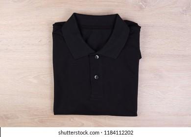 Folded black shirt polo on wooden background
