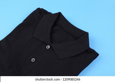 Folded black shirt polo on blue pastel background