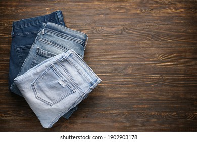 Folded blue jeans on wooden background, place for text. Top view.