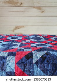 Folded Blue and Red Patchwork Quilt with Hand Quilting