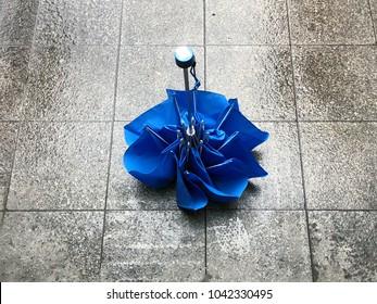 folded blue umbrella on the stone floor