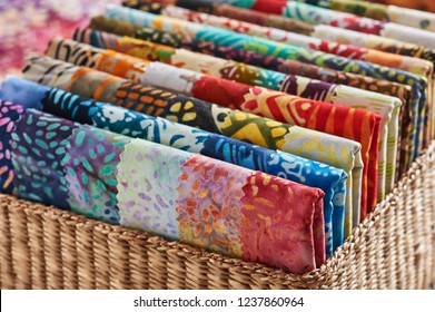 Folded bright pieces of quilting batik fabrics in a basket, macro