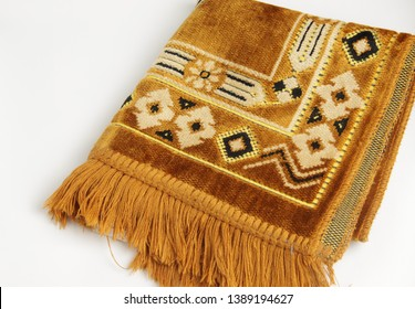 A folded brown prayer rug