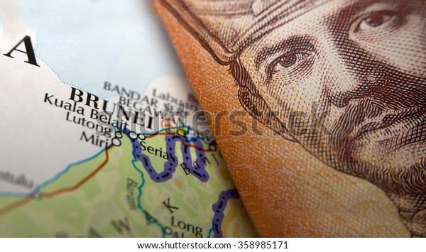 Folded Brunei Currency on top of a map of Brunei
