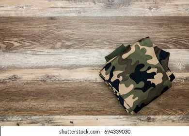 Folded camouflage pattern pants on wooden floor.