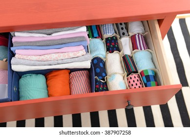 Folded clothes in chest of drawers closeup
