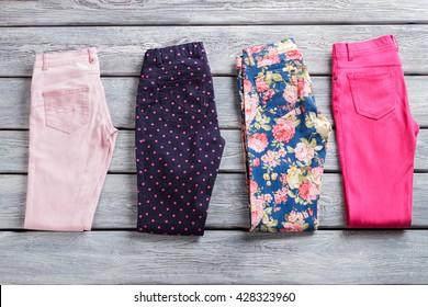 Folded colorful pants. Woman's casual trousers with print. Merchandise on gray wooden shelf. Discounted goods of high quality.