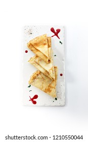 Folded Crepe or Pancakes on White Rectangular Plate with Sugar Sauce and Spices. Attractive Thin Flat Cakes also known as Blini Hotcake, Griddlecake, Flapjack, Appam or Dosa