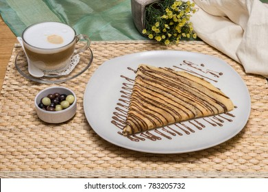 Folded crepe, Russian blini with chocolate sauce on a white plate served with cappuccino and dragees with fabric pouch and yellow flowers on background