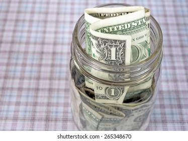 folded dollar bills in a glass mason jar