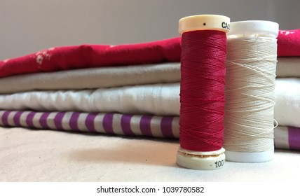Folded fabric and spools of thread. Preparation for a sewing project. Artisan's materials. Potential.