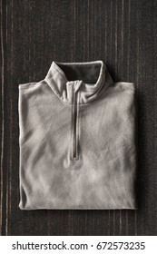 Folded gray fleece sweatshirt on dark wooden background