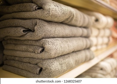 Folded grey towels on the shelf clean after loundry