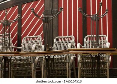 Folded group of chairs on a striped wall background.