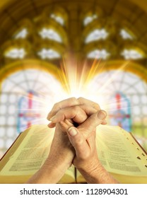 folded hands with a bible against a warm bright light and soft shining church window background