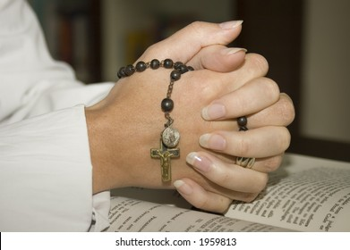 folded hands with rosary with clipping path for isolation