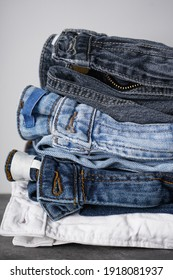 Folded jeans on gray background, vertically.